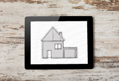 Tablet with drawing of apartment house on the screen on a backgr Stock Photo