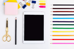 Tablet, drawing tools and stationery. Top view of blank tablet screen, colorful pencils, golden scissors, stickers and pegs on white surface. Mock up Royalty Free Stock Images