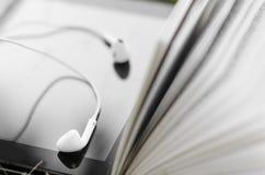 Tablet with earphones in between book Stock Photography