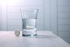 Tablet in een glas water wordt opgelost dat stock afbeelding
