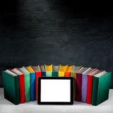 Tablet with empty screen with colorful books on background with Stock Image
