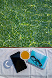 Tablet with empty screen, a glass of orange juice and blue book with glasses on the white towel. Next to the swimming pool with ripples and green mosaic tile Stock Image