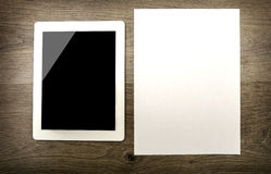 Tablet with an empty screen and paper Royalty Free Stock Images