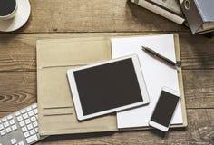 Tablet en telefoon op bureauomslag Royalty-vrije Stock Afbeeldingen