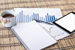 Tablet en theekop met financiële documenten Royalty-vrije Stock Afbeeldingen