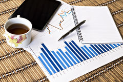 Tablet en theekop met financiële documenten Stock Afbeelding
