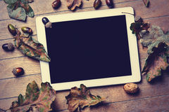 Tablet and fallen leaves Royalty Free Stock Photo