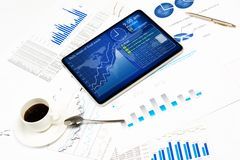Tablet, financial documents and a cup of coffee Royalty Free Stock Photography