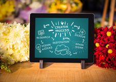Tablet on florist table showing white design doodles against teal background Stock Photo