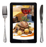 Tablet with food photo. Fork and knife, conceptual stock image