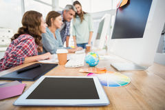Tablet in the foreground with business people in the background Royalty Free Stock Photography
