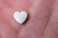 The tablet in the form of heart lay on the hand. Close up Stock Image