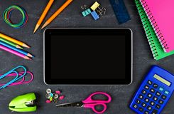 Tablet with frame of school supplies on chalkboard Stock Images