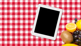 Tablet and fruit on tablecloth textile Royalty Free Stock Photography