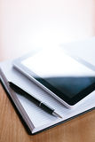 Tablet Gadget Above Notebook with Pen on Table Royalty Free Stock Images
