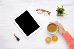 Tablet gadget, cup of coffee and muffins and lipstick on a woode Royalty Free Stock Images