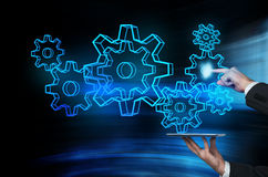 Tablet with gears and cogs. Hand holding tablet with cyber gears and cogs Stock Photo