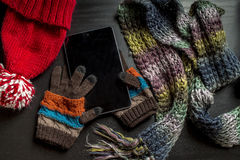 The tablet is on the gloves, as if lying in the hands of the person near to a black wooden table are other colorful winter clothes Royalty Free Stock Images