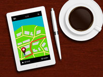 Tablet with gps navigation application, coffee and pencil lying. On wooden table Royalty Free Stock Image