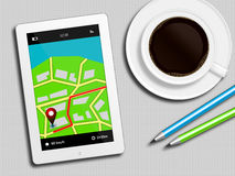 Tablet with gps navigation application, coffee and pencils lying. On white table Royalty Free Stock Images