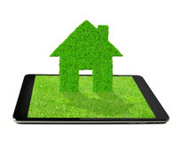 Tablet with green house Stock Images