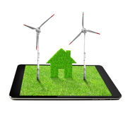 Tablet with green house and wind turbines Stock Image