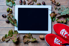 Tablet, gumshoes and fallen leaves Stock Photos