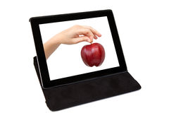 Tablet with the hand and a red apple the screen Royalty Free Stock Image