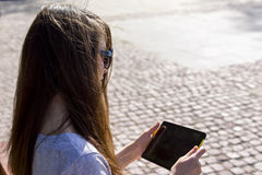 The tablet in hands of girl outside Stock Photography