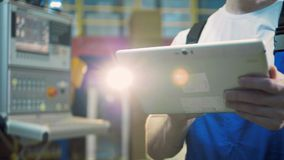 Tablet in the hands of a male worker in the factory stock video