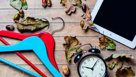 Tablet, hangers, alarm clock and fallen leaves Royalty Free Stock Image