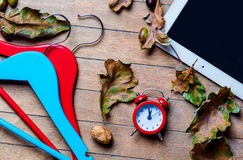 Tablet, hangers, alarm clock and fallen leaves Stock Photo