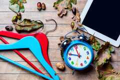 Tablet, hangers, alarm clock and fallen leaves Royalty Free Stock Photo