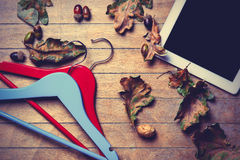 Tablet, hangers and fallen leaves Stock Photography