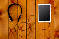 Tablet and headphone on wooden table Royalty Free Stock Photos