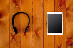 Tablet and headphone on wooden table Stock Photography