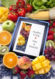 Tablet Healthy Diet Fruit Food App. A computer tablet surrounded by fresh fruit and vegetables. The screen has a healthy living food app on diet and exercise Royalty Free Stock Photo