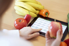 Tablet Healthy Eating Meal Planning. An ddult woman reveiwing her meal planner with a tablet PC about nutritional information of fruits and vegetables royalty free stock photo