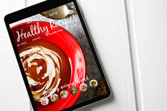 Tablet With healthy recipes blog on screen. web with nutritious. Food on white wood Royalty Free Stock Photo