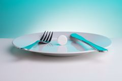 Tablet for helping to digest. Medicine for digestion concept with plate with big white tablet and for and table knife Stock Photography