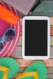 Tablet, Hut und Sonnenbrille, Pantoffel, Notizbuch auf Weinleseholz Sommerferien backgroud Stockfotografie