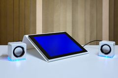 Tablet is installed in holder and connected to small speakers stock images