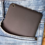 Tablet and jeans Stock Images