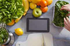Tablet on kitchen counter, copy space, fruits and vegetables next to it Stock Image