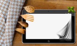 Tablet and Kitchen Utensils on a Table with Tablecloth Royalty Free Stock Image