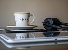 Tablet, Kopfhörer und Tasse Kaffee auf Glasschreibtisch Stockfotos