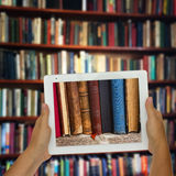 Tablet with library shelfs in background Royalty Free Stock Images