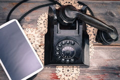Tablet lying alongside a retro rotary telephone Stock Photo