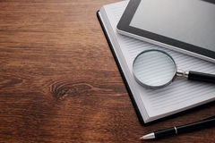 Tablet and Magnifying Glass on Notes at the Table Royalty Free Stock Images