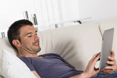 Tablet man. Man using tablet pc on sofa at home Stock Photos